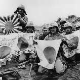 U.S. troops display captured Japanese flags during World War II.