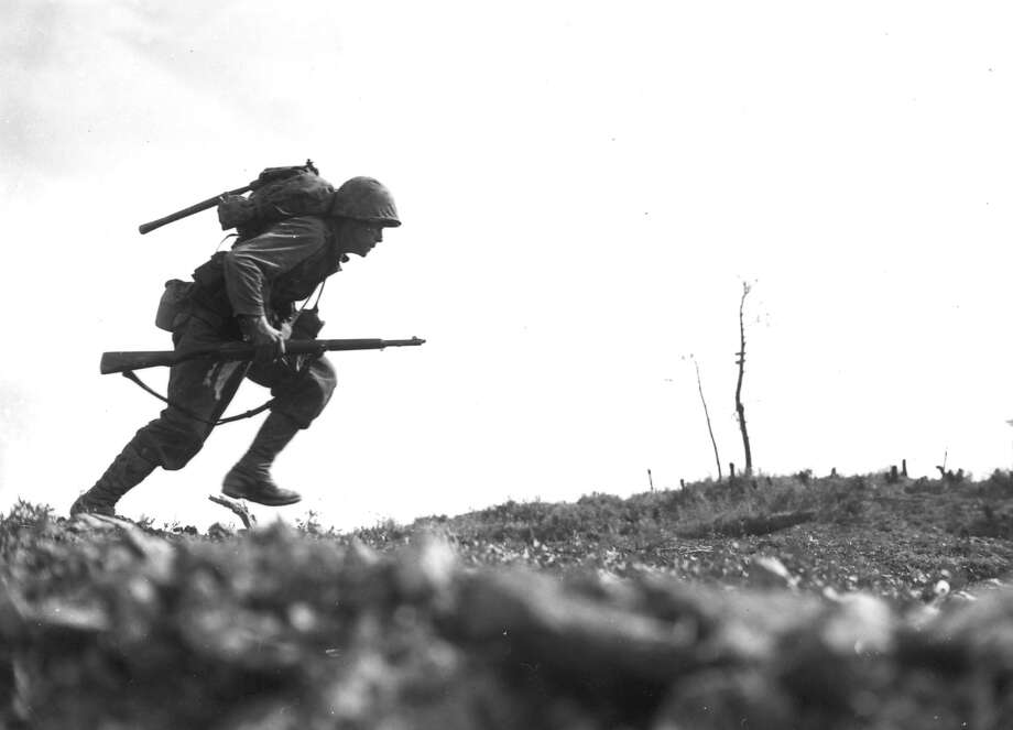 """Pfc. Paul Ison from the 6th Marine Division dashes forward through Japanese machine-gun fire while crossing a draw on Okinawa, May 10, 1945.  After the Marines sustained more than 125 casualties in eight hours in the attempt to cross this draw, the men named the location """"Death Valley."""" Photo: ASSOCIATED PRESS / AP1945"""