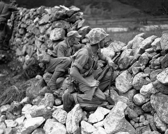 Two U.S. soldiers are on the alert as they take protection behind stone wall on Korean front near Choyang River in North Korea on June 3, 1951. Cpl. Richard G. Clark, foreground, of Westwood, New Jersey, wears helmet as Pfc. Joseph M. Nadorozny, of 973 east 13th St., Brooklyn, New York, puffs on cigarette. Photo: E.N.Johnson, AP / AP1951