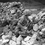 Two U.S. soldiers are on the alert as they take protection behind stone wall on Korean front near Choyang River in North Korea on June 3, 1951. Cpl. Richard G. Clark, foreground, of Westwood, New Jersey, wears helmet as Pfc. Joseph M. Nadorozny, of 973 east 13th St., Brooklyn, New York, puffs on cigarette.
