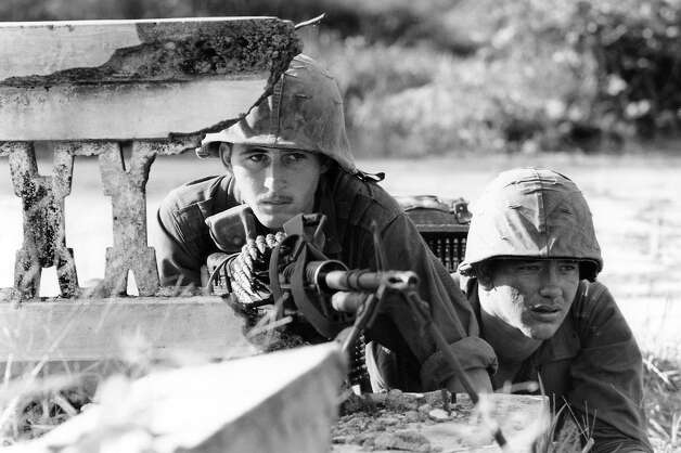 Spec. 4 James D. McClafferty of Philadelphia and Pfc. Ted Talley of Marked Tree, Ark., man a machine gun in the ruins of a house near Rach Kien, 22 miles southwest of Saigon, Jan. 2, 1966. Their company, operating in the delta province of Long An, came under fire when they approached a farmhouse at the edge of an abandoned town. Photo: Horst Faas, AP / 1966 AP