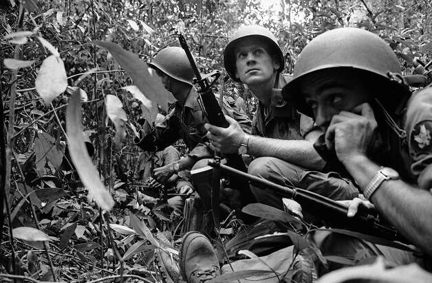 SP4 Nelson A. Parker uses field phone to call for air power as Vietnamese patrol is surrounded by Communist Viet Cong in jungle 20 miles north of Saigon in Vietnam on Feb. 15, 1965. Beside him is Sgt. Lloyd E. Rath. Both were U.S. advisers with the patrol. Eighteen Red guerrillas were killed in the battle. Parker's parents live in Paul Smiths, New York. Rath's wife lives in Ephrata, Pa.; his mother in Jamestown, North Dakota. Photo: Anonymous, AP / AP1965