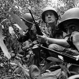 SP4 Nelson A. Parker uses field phone to call for air power as Vietnamese patrol is surrounded by Communist Viet Cong in jungle 20 miles north of Saigon in Vietnam on Feb. 15, 1965. Beside him is Sgt. Lloyd E. Rath. Both were U.S. advisers with the patrol. Eighteen Red guerrillas were killed in the battle. Parker's parents live in Paul Smiths, New York. Rath's wife lives in Ephrata, Pa.; his mother in Jamestown, North Dakota.