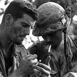 Commanders of two U.S. Marine companies who had been surrounded for two days by the North Vietnamese 324 Division eight miles south of the demilitarized zone, pause for a cigarette after other American units came to their aid, Sept. 20, 1966. They are 1st Lt. Daniel McMahon , left, of Oceanside, N.Y., who leads Delta Co., and Capt. Ronald Frederickson, South Sioux City, Neb, commander of Bravo Co. Sept. 20, 1966.