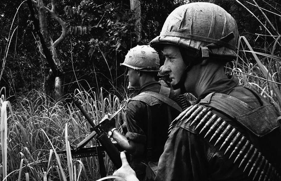 Two American paratroopers keep a sharp eye out for guerrillas and snipers as they patrol the jungle in D zone, some 20 miles northeast of Bien Hoa, Vietnam on May 31, 1965. They are members of an artillery battery and a battalion of paratroopers from the U.S. 173rd Airborne Brigade which were lifted by helicopter in the zone along a stronghold of the Viet Cong. Photo: Horst Faas, AP / 1965 AP