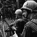 Two American paratroopers keep a sharp eye out for guerrillas and snipers as they patrol the jungle in D zone, some 20 miles northeast of Bien Hoa, Vietnam on May 31, 1965. They are members of an artillery battery and a battalion of paratroopers from the U.S. 173rd Airborne Brigade which were lifted by helicopter in the zone along a stronghold of the Viet Cong.