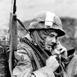 Bundled against the chill a U.S. Marine reports to his headquarters on a radiotelephone during operation Kentucky near the demilitarized zone in South Vietnam on Dec. 11, 1967. Monsoon rains and temperatures that drop into the 40s and 50s at night make life miserable for the U.S. soldiers  in the Northern provinces.