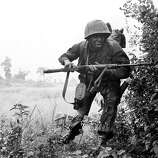An infantryman of the U.S. 25th Division rushes for cover as he comes under sniper fire near the village of Rach Kien, 20 miles southwest of Saigon in Vietnam's Mekong Delta, in 1967 during the Vietnam War.