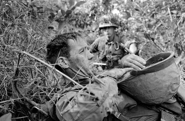 Pfc. James F. Duro of Boston, Mass., a member of C Company, 173rd Airborne Brigade, lies exhausted on a canal dike in the swampland of the Mekong Delta near Bao Trai, about 20 miles west of Saigon, on Jan. 4, 1966. An hour Duro survived friendly fire from a misdirected artillery bombardment that, in addition to enemy fire, left fellow soldiers dead and wounded. Photo: Horst Faas, AP / A1966