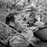 Pfc. James F. Duro of Boston, Mass., a member of C Company, 173rd Airborne Brigade, lies exhausted on a canal dike in the swampland of the Mekong Delta near Bao Trai, about 20 miles west of Saigon, on Jan. 4, 1966. An hour Duro survived friendly fire from a misdirected artillery bombardment that, in addition to enemy fire, left fellow soldiers dead and wounded.