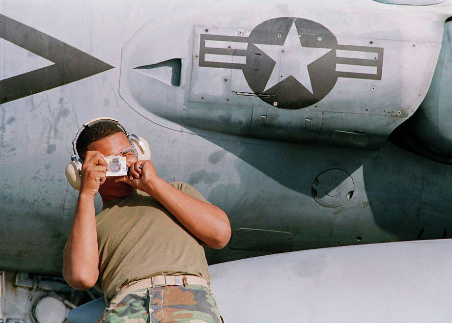 A U.S. Marine Harrier ground crew member, who would not be identified, shoots a souvenir picture as his Harrier squadron prepares to leave Dhahran, Saudi Arabia, Friday, March 15, 1991, for their return to the Cherry Point, N.C., Marine Air Station. Photo: Bob Jordan, ASSOCIATED PRESS / AP1991
