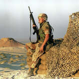 U.S. soldier rests while on guard at a relay station in the Saudi Arabian dessert during operation Desert Shield, November 9, 1990.
