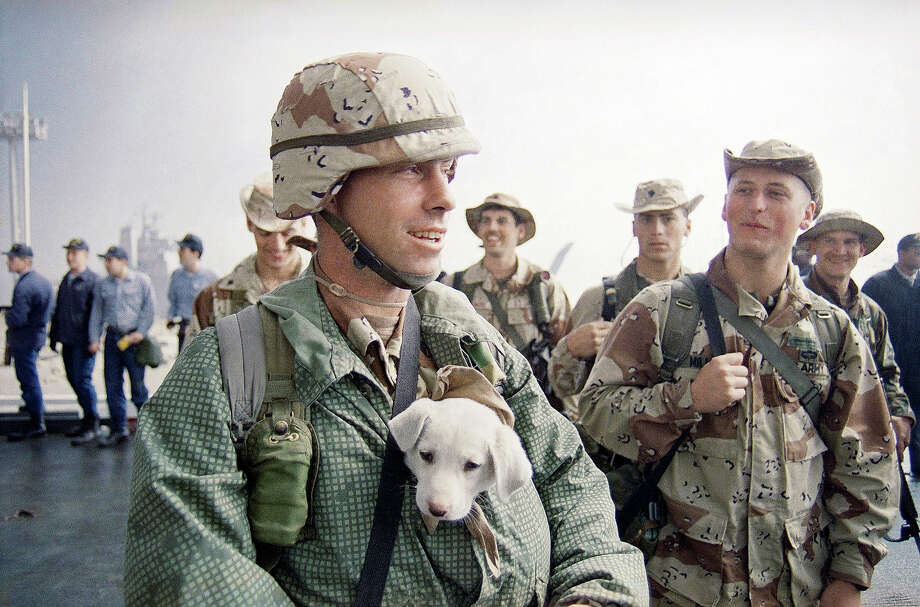 U.S. Army Sgt. John Cobb of Newport Beach, Calif., keeps his dog, J.C., warm inside his coat while waiting for the arrival of the U.S. command ship, the U.S.S. LaSalle, in Kuwait City on Tuesday, March 12, 1991. Photo: Greg Gibson, ASSOCIATED PRESS / AP1991