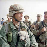 U.S. Army Sgt. John Cobb of Newport Beach, Calif., keeps his dog, J.C., warm inside his coat while waiting for the arrival of the U.S. command ship, the U.S.S. LaSalle, in Kuwait City on Tuesday, March 12, 1991.