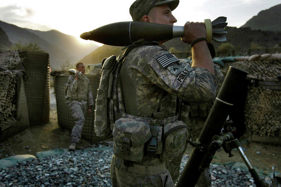 CPL Jeremy Foley of Bloomington, IL and fellow U.S. soldiers from the 2nd Battalion, 12th Infantry Regiment, 4th Brigade Combat Team, 4th Infantry Division prepare to fire mortars in the Pech Valley of Afghanistan's Kunar province Monday, Oct. 26, 2009. Photo: David Guttenfelder, ASSOCIATED PRESS / AP2009