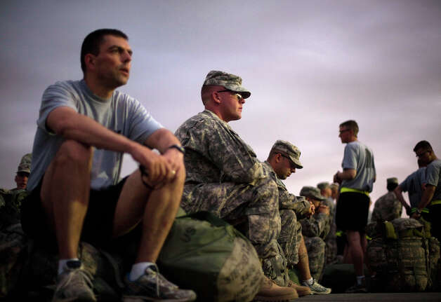 Sgt. Dave Carbary, 24, center, of Sterling Heights, Mich., with the U.S. Army's 4th Brigade Combat Team, 101st Airborne Division out of Fort Campbell, Ky., waits with fellow soldiers to have his luggage checked by U.S. Customs at the Transit Center in Manas, Kyrgyzstan, while continuing home after leaving Afghanistan upon completing a deployment, Monday, Aug. 8, 2011. The 4th Brigade Combat Team, 101st Airborne Division is returning home after a year in Afghanistan as the last brigade to deploy as part of President Obama's 30,000 troop surge. Photo: David Goldman, ASSOCIATED PRESS / AP2011