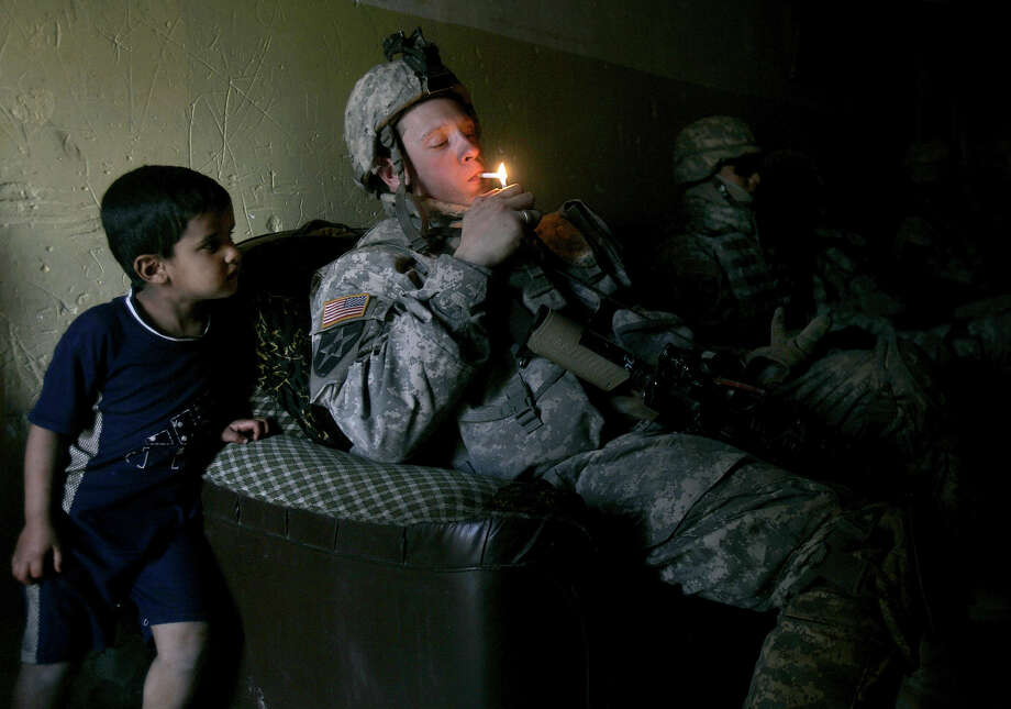 An Iraqi boy watches as a U.S. army soldier from B Company, 1st Battalion, 23rd Infantry Regiment lights up a cigarette as members of his unit take a rest after a foot patrol in Baghdad's Shiite enclave of Sadr City, Iraq, Saturday, March 17, 2007. Photo: MARKO DROBNJAKOVIC, ASSOCIATED PRESS / AP2007