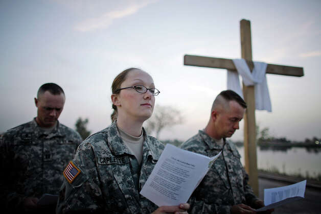 US soldiers read verses as they celebrate  Easter with a sunrise service at Camp Victory, in Baghdad, Iraq, Sunday, March 23, 2008. Suspected Shiite extremists fired two barrages Sunday at the U.S.-protected Green Zone, and a suicide bomber stuck an Iraqi army position in northern Iraq, killing 10 Iraqi soldiers and wounding 50 others. Photo: DUSAN VRANIC, ASSOCIATED PRESS / AP2008