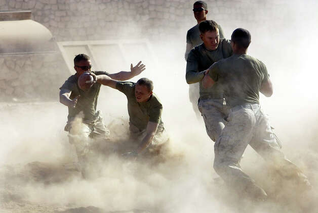 U.S. Marines play football in Karabilah, an Iraqi town near the Syrian border, Thursday, Nov. 24, 2005. Thursday, Americans celebrated Thanksgiving. Photo: JACOB SILBERBERG, ASSOCIATED PRESS / AP2005