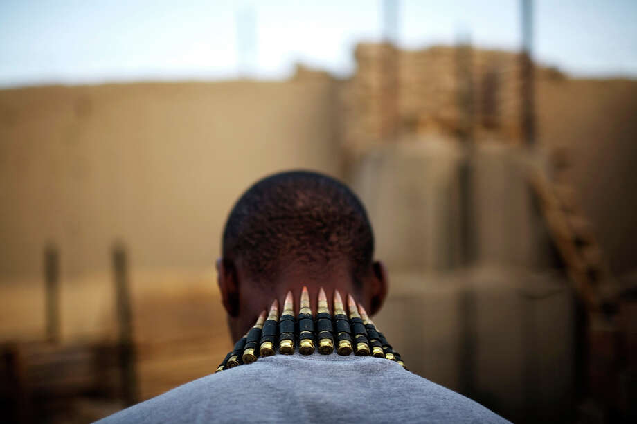 A string of bullets hangs on the neck of US Army soldier PFC Jean-Paul Desculline , of Miami, Florida, from 1-320th Alpha Battery, 2nd Brigade of the 101st Airborne Division, at COP Nolen, in the volatile Arghandab Valley, Kandahar, Afghanistan, Sunday, July 25, 2010. Photo: Rodrigo Abd, ASSOCIATED PRESS / AP2010