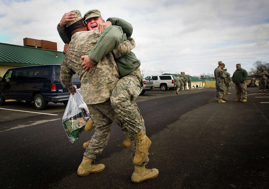Spc. John Lundy, right, and Spc. Matthew Sturgill, obscured, leap into the arms of PFC Devin Horton, left, Friday, Dec. 23, 2011, at Camp Atterbury in Edinburgh, Ind., as 109 members of the 1st Battalion, 149th Infantry, National Army Guard, prepare to board a bus home to Kentucky and join their families for the holidays. As part of the last soldiers to leave Iraq, the men arrived at Camp Atterbury on Dec. 21. The U.S. military announced Saturday, Dec. 17, 2011,  that the last American troops have left Iraq as the nearly nine-year war ends. Photo: AP