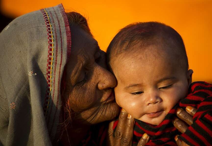 Nana's little man: A Pakistani nomad woman named Zakia kisses her grandson in Islamabad.