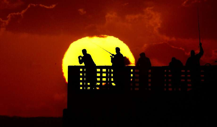 Back in business: Fishermen cast off the Lake Worth Pier at sunrise in Lake Worth, Fla. The pier reopened Friday after being closed for two weeks from damage caused by Hurricane Sandy. Photo: Lannis Waters, Associated Press