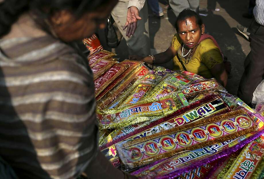 Bless this concession stand: An Indian transsexual prepares to give a blessing to a roadside vendor selling items for the upcoming Diwali holiday at a market in New Delhi. Photo: Kevin Frayer, Associated Press