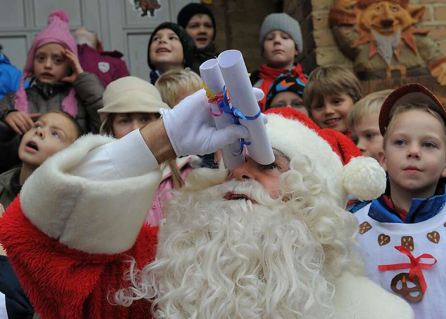 "I can see flakes! Santa looks for snow with his ""binoculars"" outside the post office in Himmelpfort, Germany. Note the two kids behind him going, ""Where? Where?"" Photo: Bernd Settnik, AFP/Getty Images"