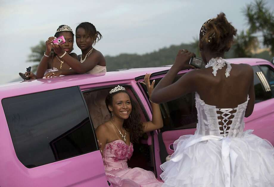 Girls turning 15 pose in their gowns inside a pink limousine before their debutante ball in the Mangueira favela, or shantytown, of Rio de Janeiro. Photo: Silvia Izquierdo, Associated Press