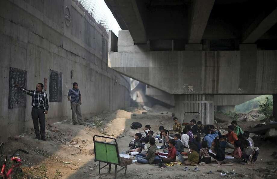 Sitting in the dirt, slum children attend class under an overpass in New Delhi. The free school is run by teachers Rajesh Kumar Sharma (left) and Laxmi Chandra (center). Photo: Altaf Qadri, Associated Press