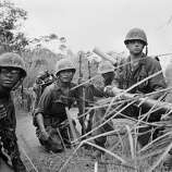 U.S. Marines of the 7th Fleet's special landing team, the 1st Battalion, 26th Marines, crouch on a dirt trail with a 3.5 inch rocket launcher about one mile (2000 meters) south of the demilitarized zone (DMZ) as they respond to sniper fire during Operation Prairie against the North Vietnamese 324B Division, September 1966.