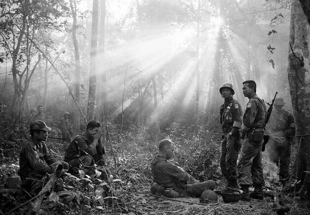 The sun breaks through the dense jungle foliage around the embattled town of Binh Gia, 40 miles east of Saigon, in early January 1965, as South Vietnamese troops, apparently joined by U.S. advisers, rest after a cold, damp and tense night of waiting in an ambush position for a Viet Cong attack that didn't come. One hour later, as the possibility of an overnight attack by the Viet Cong disappeared, the troops moved out for another long, hot day hunting the elusive communist guerrillas in the jungles. Photo: AP