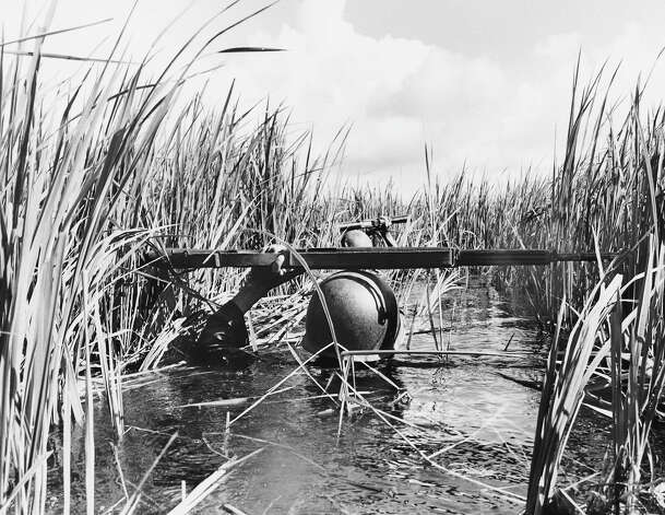 Resting his rifle on his steel helmet to relieve his weary arm, a South Vietnamese soldier plods through deep water of the Mekong River Delta on a mission to ferret out bands of Viet Cong in October 1964. The government troops were ferried into the region by helicopter, but failed to make contact with the enemy after wading through acres of water and mud. Photo: AP