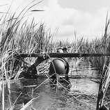 Resting his rifle on his steel helmet to relieve his weary arm, a South Vietnamese soldier plods through deep water of the Mekong River Delta on a mission to ferret out bands of Viet Cong in October 1964. The government troops were ferried into the region by helicopter, but failed to make contact with the enemy after wading through acres of water and mud.
