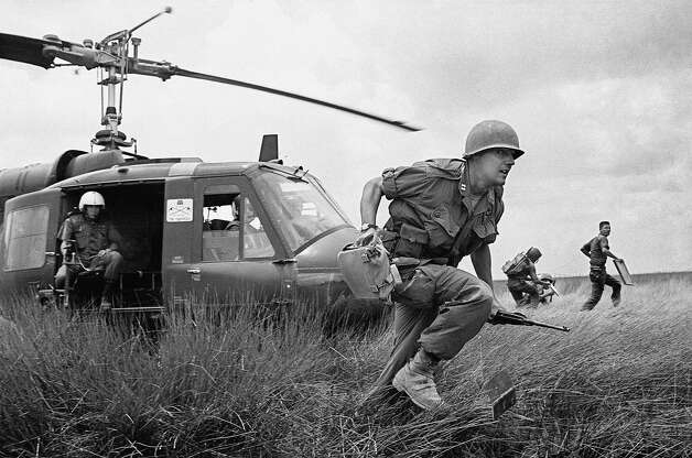 Capt. Donald R. Brown of Annapolis, Md., advisor to the 2nd Battalion of the 46th Vietnamese regiment, dashes from his helicopter to the cover of a rice paddy dike during an attack on Viet Cong in an area 15 miles west of Saigon on April 4, 1965 during the Vietnam War.  Brown's counterpart, Capt. Di, commander of the unit, rushes away in background with his radioman.  The Vietnamese suffered 12 casualties before the field was taken. Photo: AP
