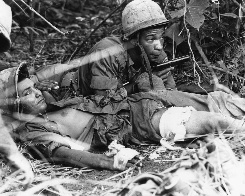 After their unit landed in the middle of a Viet Cong staging area, medic Pfc. Andrew J. Brown of Chicago draws his pistol while protecting a wounded U.S. paratrooper from sniper fire in the jungle near Thuong Lang, about 10 miles northeast of Bien Hoa, June 24, 1965. Brown and another medic crawled through the jungle to treat the paratrooper while a live grenade lay nearby. Photo: AP