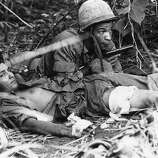 After their unit landed in the middle of a Viet Cong staging area, medic Pfc. Andrew J. Brown of Chicago draws his pistol while protecting a wounded U.S. paratrooper from sniper fire in the jungle near Thuong Lang, about 10 miles northeast of Bien Hoa, June 24, 1965. Brown and another medic crawled through the jungle to treat the paratrooper while a live grenade lay nearby.
