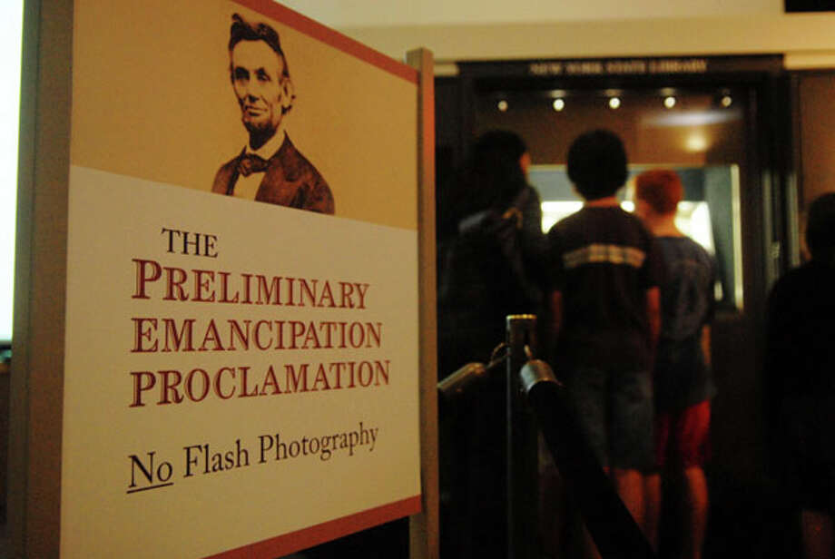 Visitors gather to look over the handwritten copy of President Abraham Lincoln's  Preliminary Emancipation Proclamation on display at the New York State Museum in Albany, NY on Sunday, Sept. 19, 2010, during a public display of the document.  The document is encased surrounded by nitrogen gas with special lighting to help protect the document from degrading.  The document is part of the New York State Library?s collection.  (Paul Buckowski / Times Union)