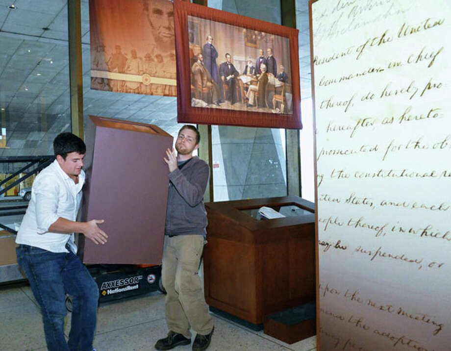 "Museum exhibit specialists Nicholas Blais, left, and Alan Noble set up ""The First Step to Freedom: Abraham Lincoln's Preliminary Emancipation Proclamation"" exhibition at the State Museum Thursday Nov. 8, 2012.  (John Carl D'Annibale / Times Union)"