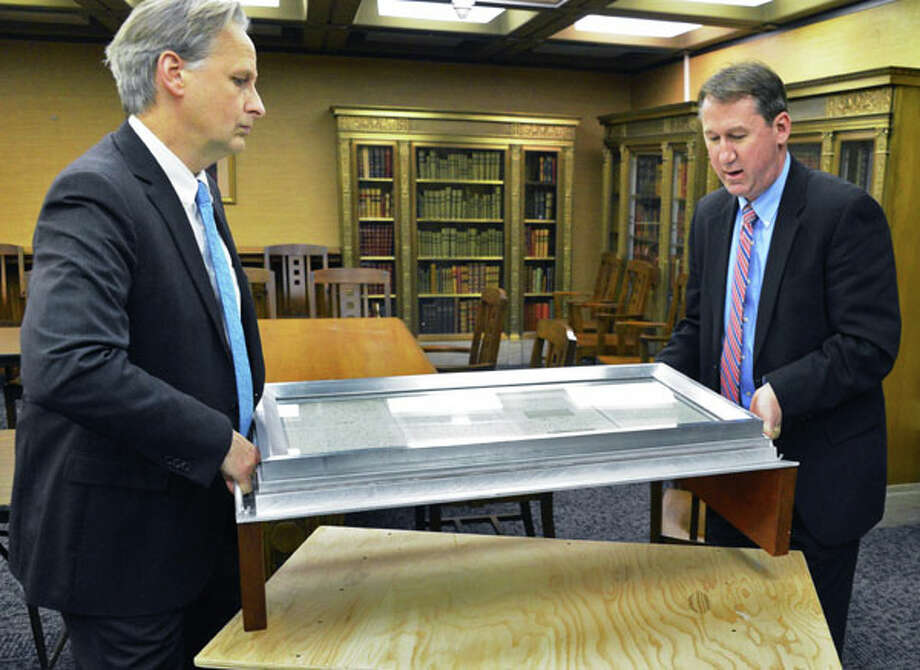 Museum director Mark Schaming, left, and director of operations for the museum's cultural education center, Thomas Ruller, carry the Preliminary Emancipation Proclamation from the State Museum's vault on Thursday Nov. 8, 2012.  (John Carl D'Annibale / Times Union)