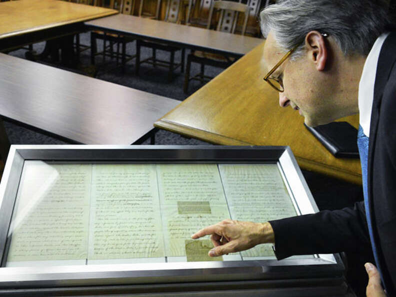 Museum director Mark Schaming examines Abraham Lincoln's handwrittten emancipation proclamation at t