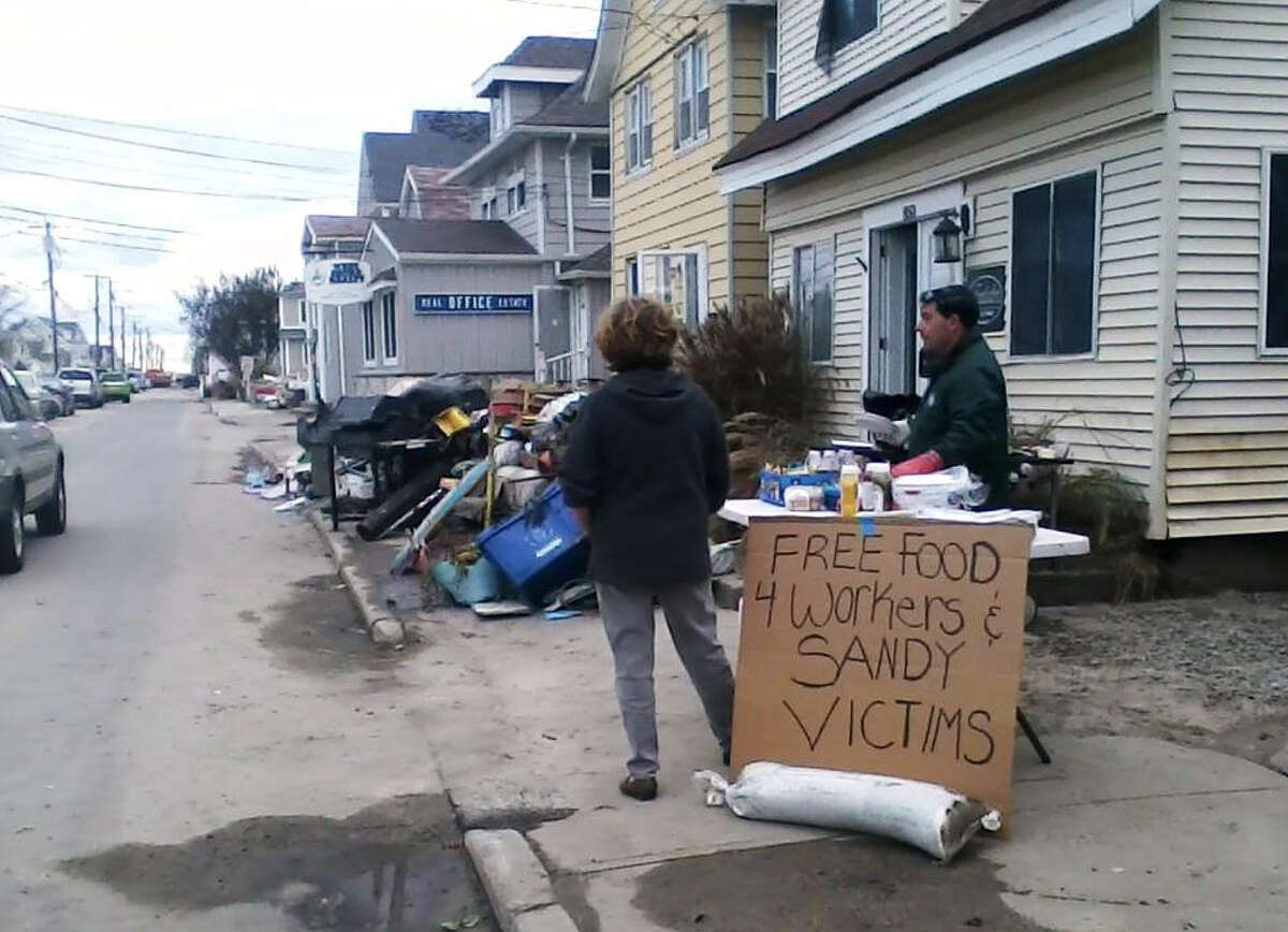 Carl Loschiavo, owner of the house shown behind him on East Broadway in Milford, took to a grill on Friday and Saturday after the passing of Hurricane Sandy to cook hot dogs and hamburgers for residents and emergency workers.