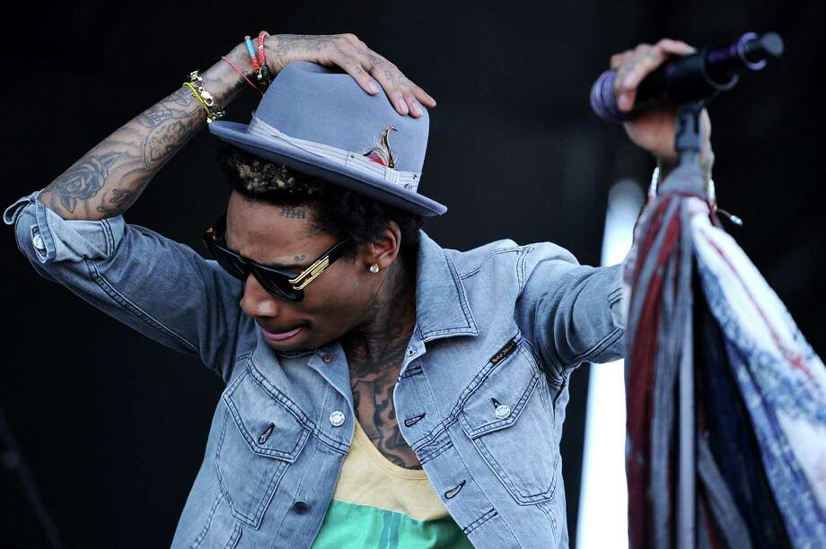 "Wiz Khalifa sings ""Young, Wild & Free"" in Baltimore. His song ""Work Hard, Play Hard,"" especially the work part, seems to define the performer. Getty Images Photo: Patrick Smith, Getty Images / 2012 Getty Images"