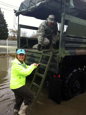 Kathy Niznansky climbs into the back of a National Guard vehicle last Thursday to be driven home follwoing flooding caused by Sandy. Her daughter, Kelly,  has helped organize a community cleanup in the Fairfield Beach neighborhood this Sunday. Photo: Contributed Photo