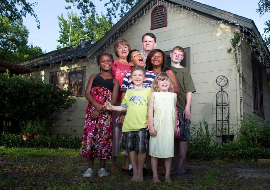 Sylvia and Bob Hollingsworth stand with their children, clockwise from left, Allie, 7, James, 10, Sariah, 11, John, 14, Rachel, 5 and Anthony, 6.  At right, Rachel, left, holds Allie's hand as they walk to school for Rachel's first day at Browning Elementary School. Photo: Cody Duty, Staff / Houston Chronicle