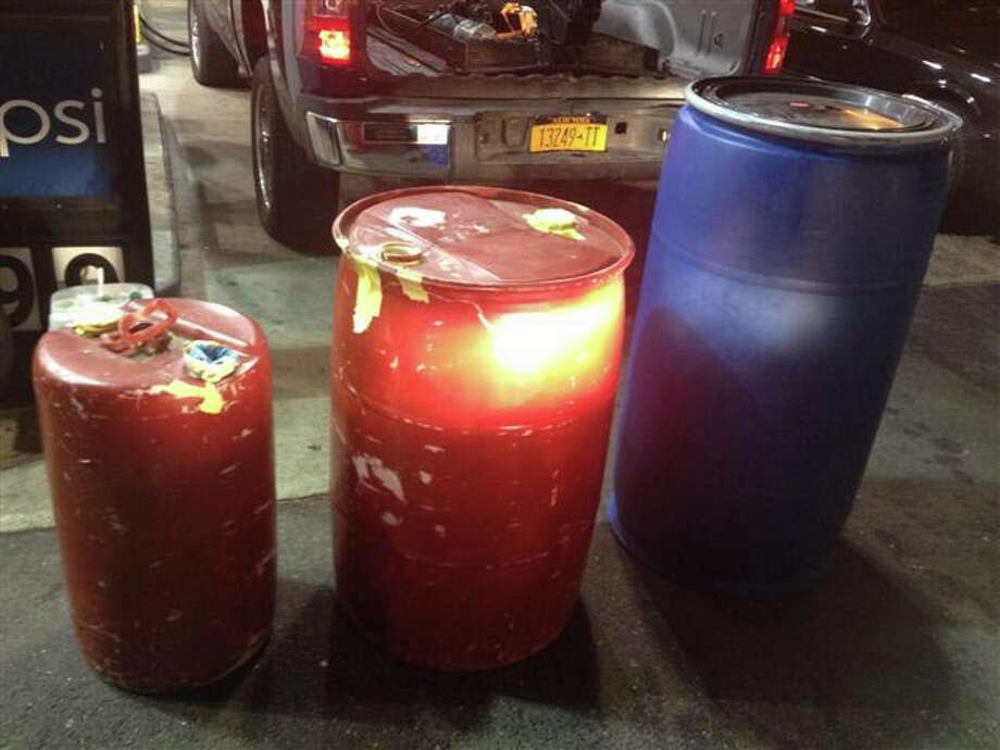 Police said a New York man pumped $400 worth of gasoline into these three unapproved containers Tuesday. The gas was returned to the station's tanks after police and firefighters arrived on the scene. Photo: Contributed Photo / Fairfield Citizen