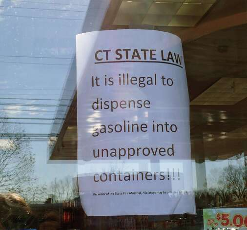 Signs warning customers about dispensing gasoline into unauthorized containers are posted on gas station doors in Fairfield. Fairfield, CT 11/9/12 Photo: Genevieve Reilly / Fairfield Citizen