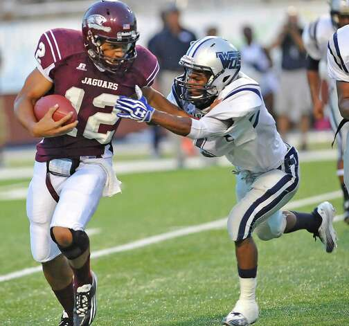 "Central's #12, Robert Mitchell, left, tries to avoid WO-S #20, Travon Blanchard, right, as he tries to gin some yardage. The West Orange-Stark football team played Central Medical Magnet High School Friday night, September 14, 2012 at the Carrol A. ""Butch"" Thomas Educational Support Center. At the half, WO-S was ahead 7-0. This is a nondistrict game.  Dave Ryan/The Enterprise Photo: Dave Ryan"