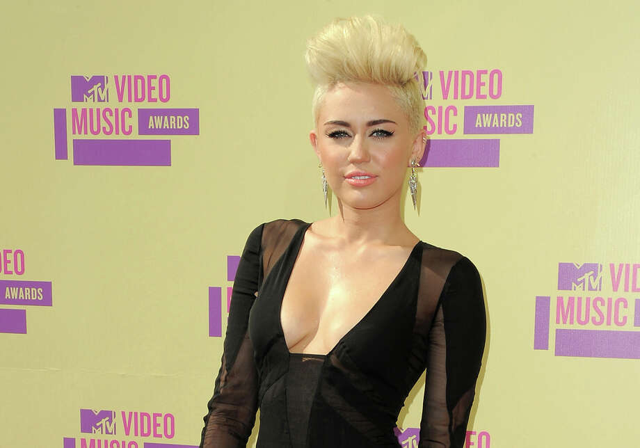 FILE - In this Sept. 6, 2012 file photo, Miley Cyrus attends the MTV Video Music Awards in Los Angeles. Cyrus is hard at work on a new album, though no title or release date have been announced. She says she doesn't stray too far from her country roots, but the album has more of a hip-hop sound. (Photo by Jordan Strauss/Invision/AP, file) Photo: Jordan Strauss